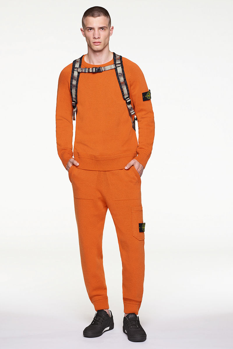 Front view of model wearing orange sweater with matching pants, black and white sneakers and multi colored backpack.