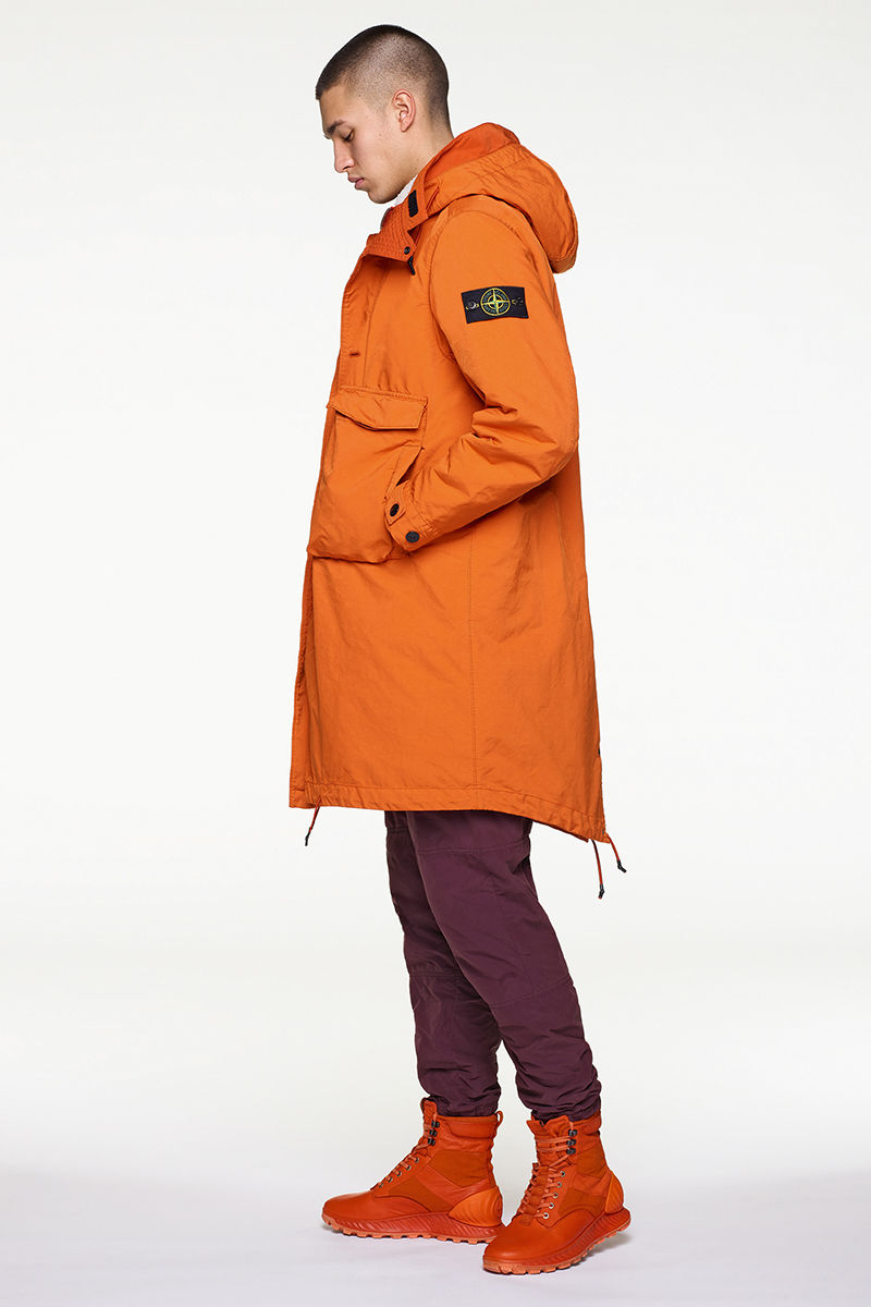Side view of model wearing orange parka with Stone Island badge on left arm, dark burgundy pants and orange high top sneakers.