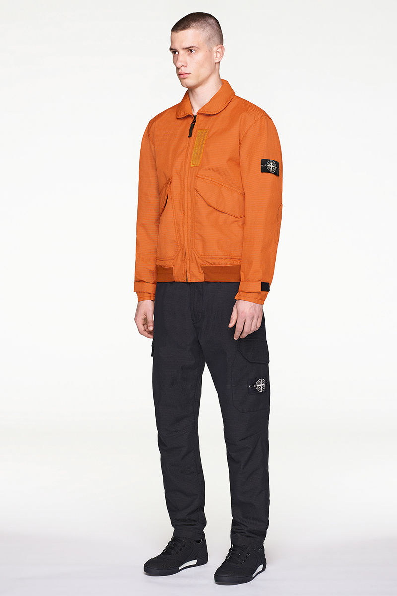 Model wearing orange bomber jacket with black pants and black and white sneakers.