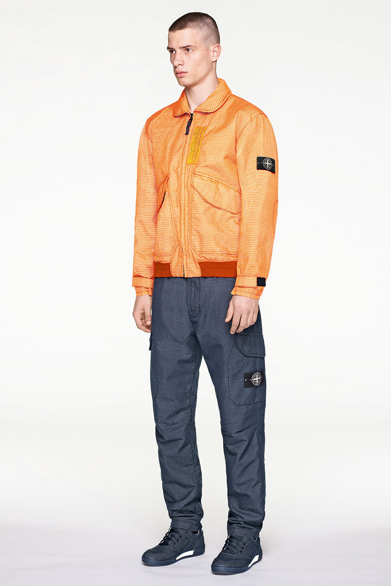 Model wearing bomber jacket in orange, jacquard fabric with dark gray pants and sneakers.