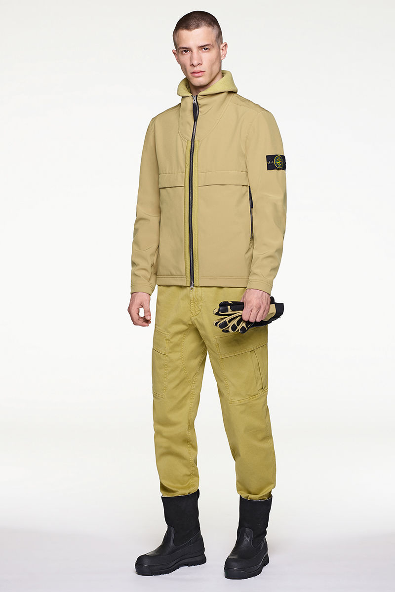 Model wearing ecru jacket with Stone Island badge on left arm, ecru pants and black boots.