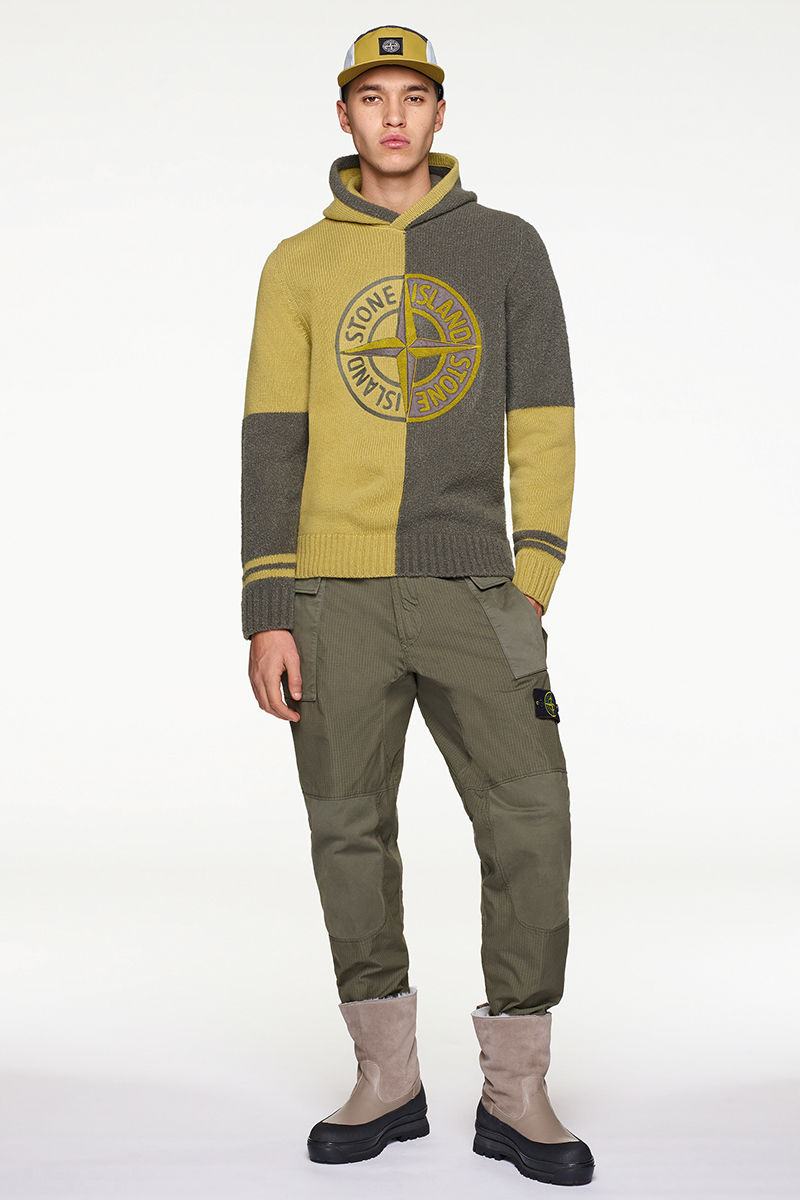 Model wearing mustard and dark green knit sweater with dark green pants, cap and black and sand colored boots.