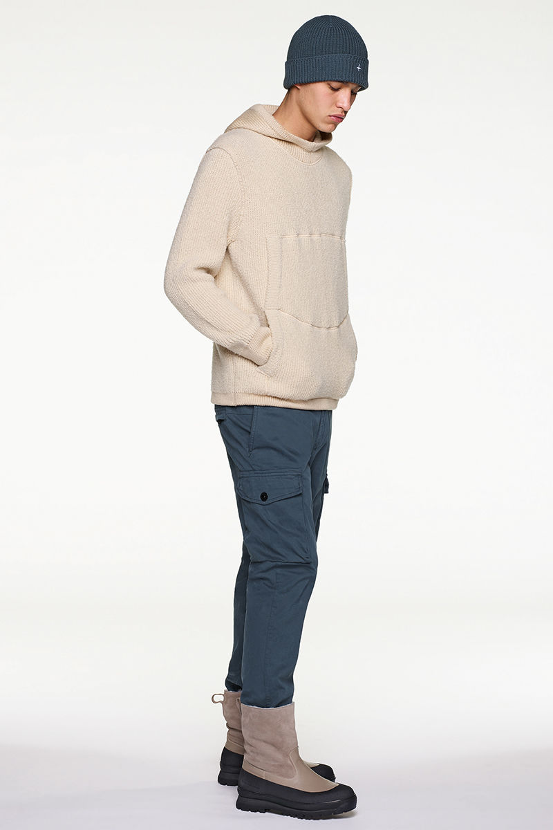 Model wearing cream sweater, blue beanie and pants and black and sand colored boots.