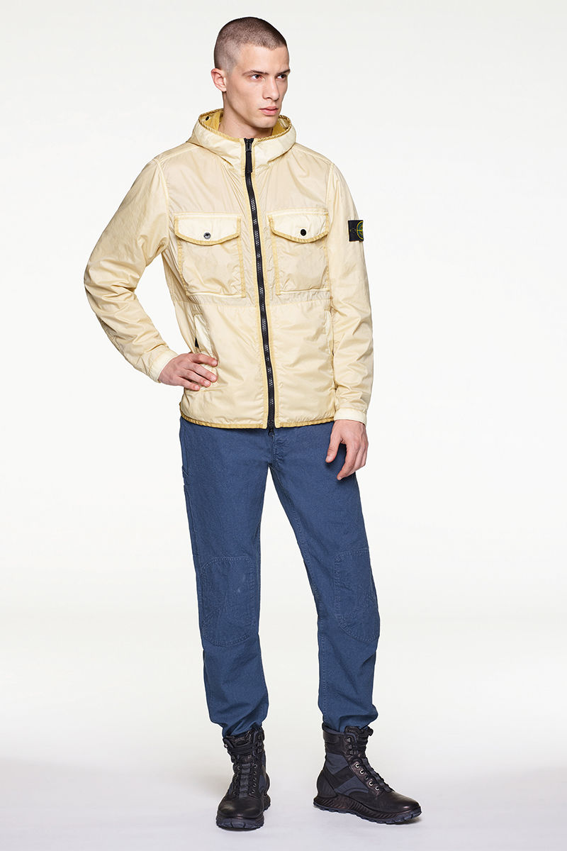 Model wearing pale yellow jacket, blue pants and black high top sneakers.
