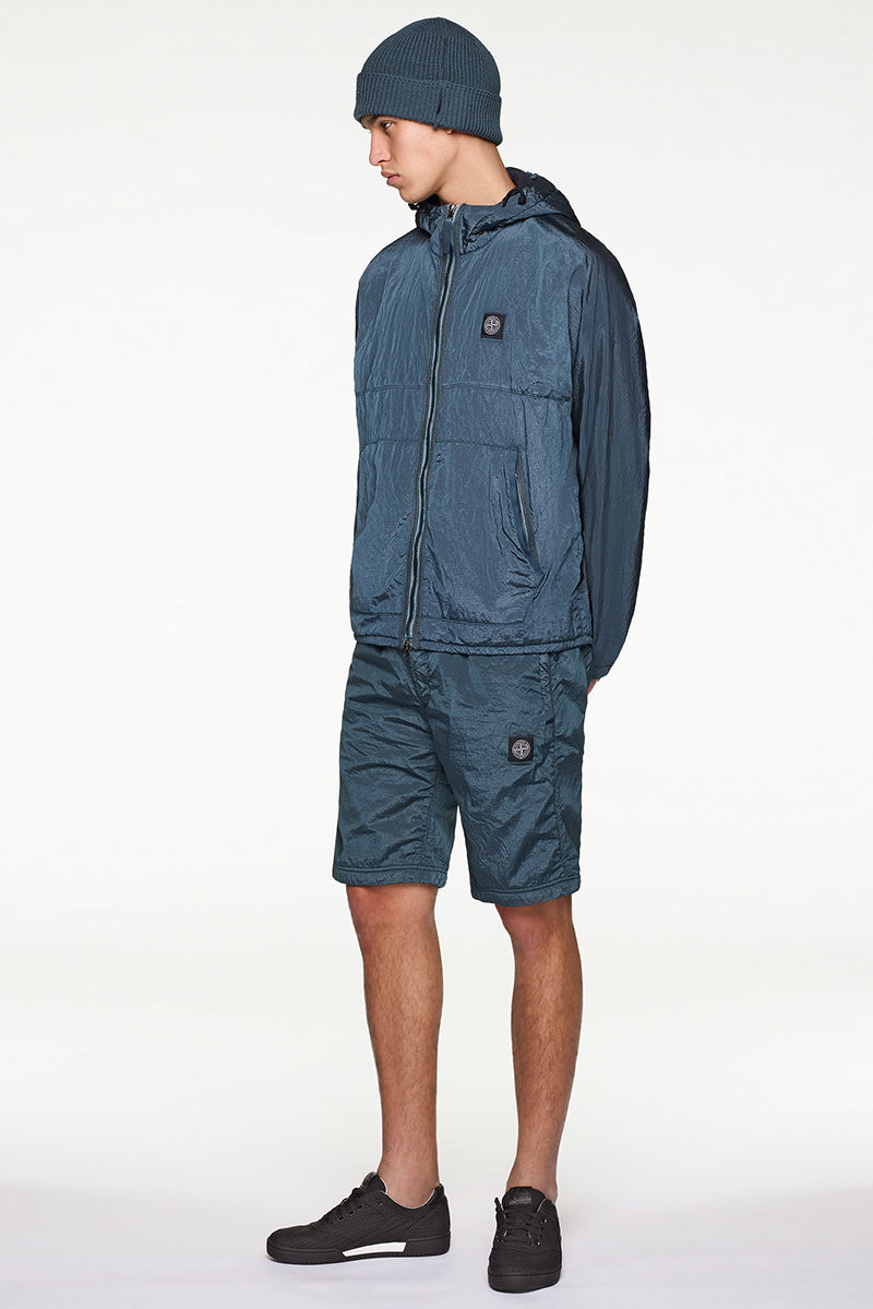 Model wearing blue beanie, blue jacket and blue bermuda shorts, both with Stone Island patch.
