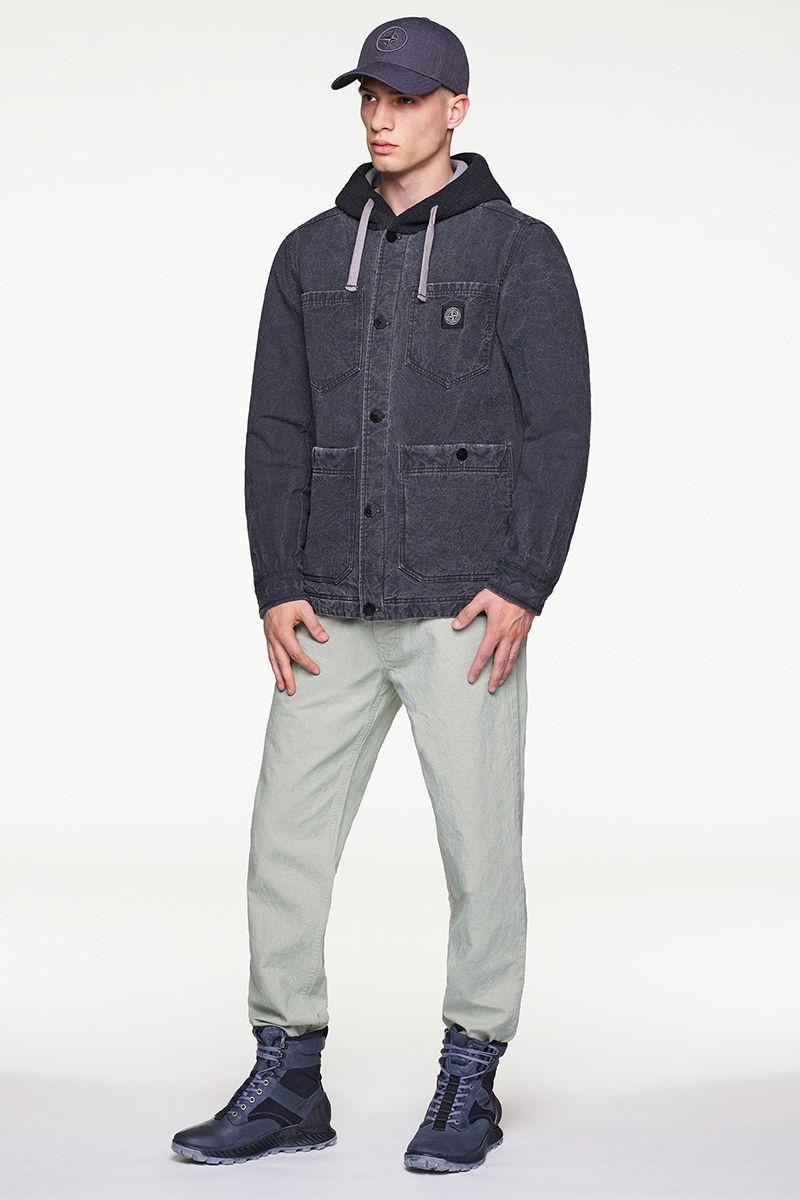Model wearing dark colored jacket over hoodie, off white pants, cap and black, high top sneakers.