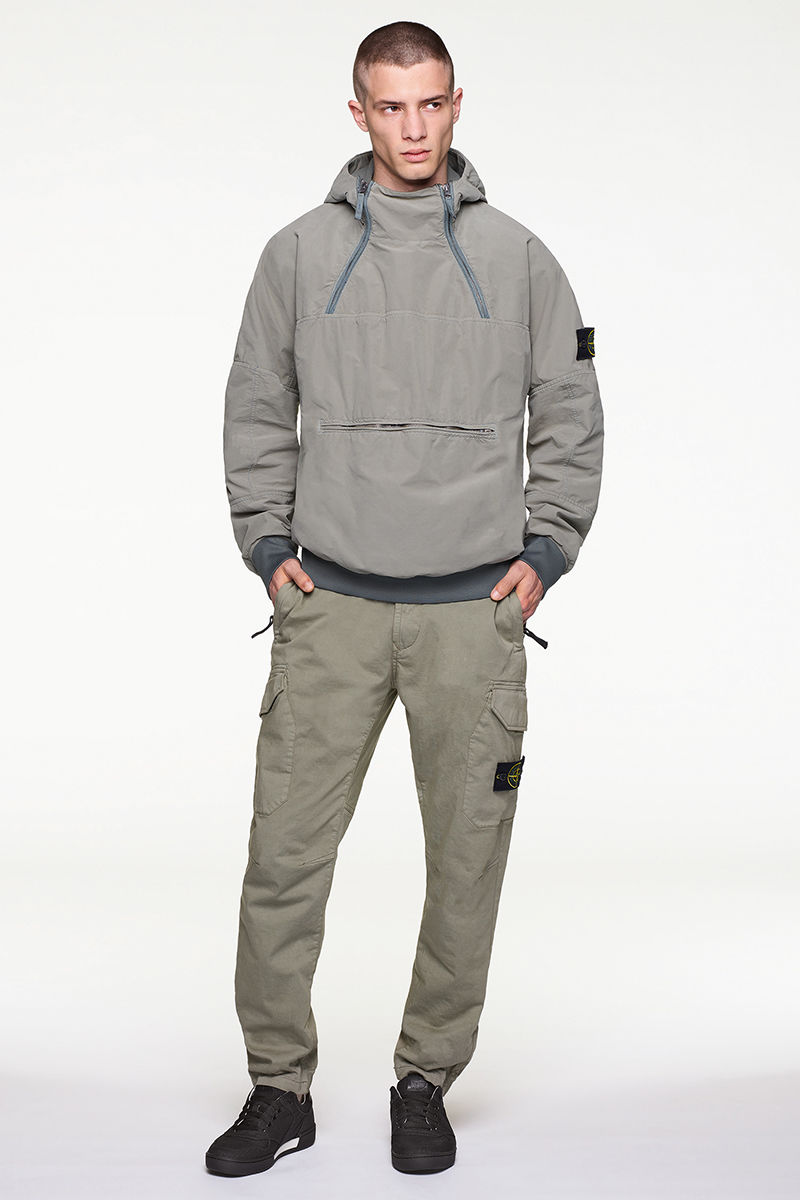 Model wearing gray hooded anorak with two zippers at chest, pants with Stone Island badge on left thigh and black sneakers.