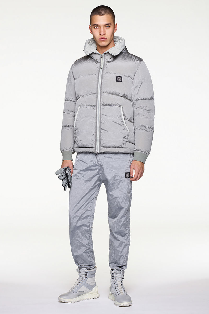 Model wearing gray puffer jacket, gray pants and gray high top sneakers.