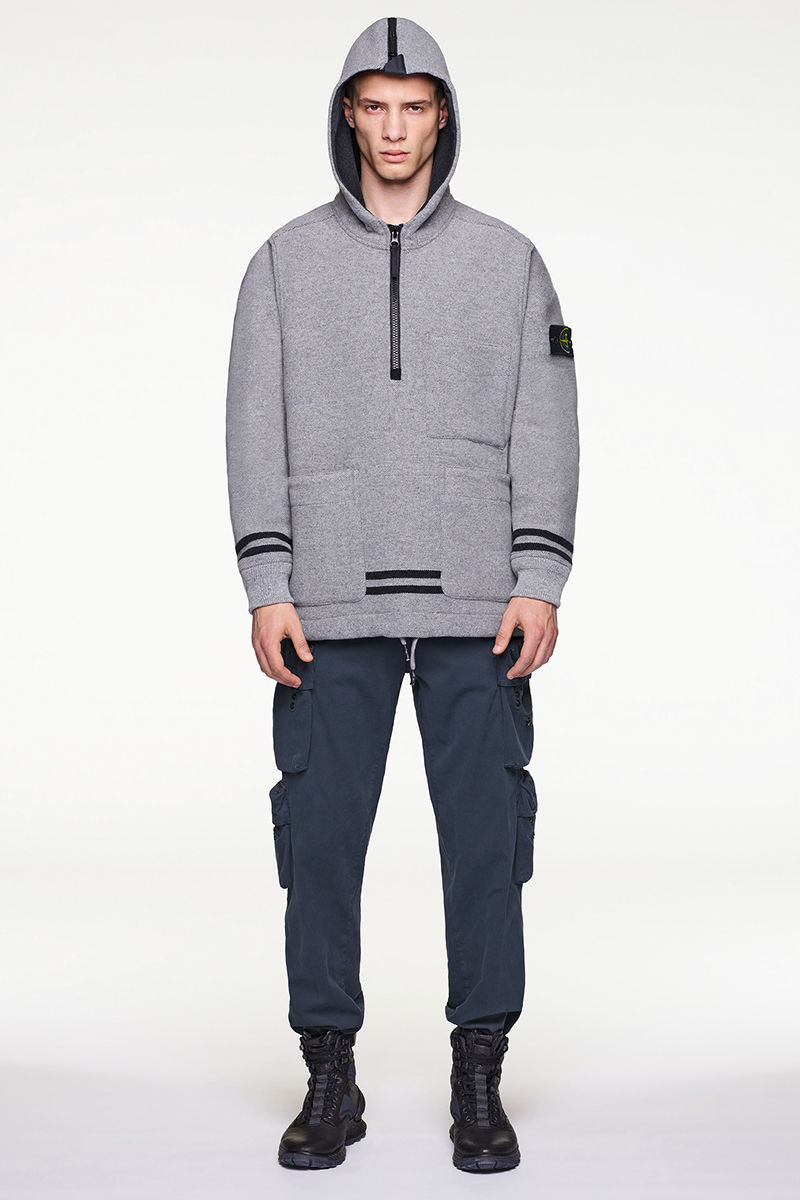Front view of model wearing gray hooded sweater with dark stripes, blue pants and black and blue high top sneakers.