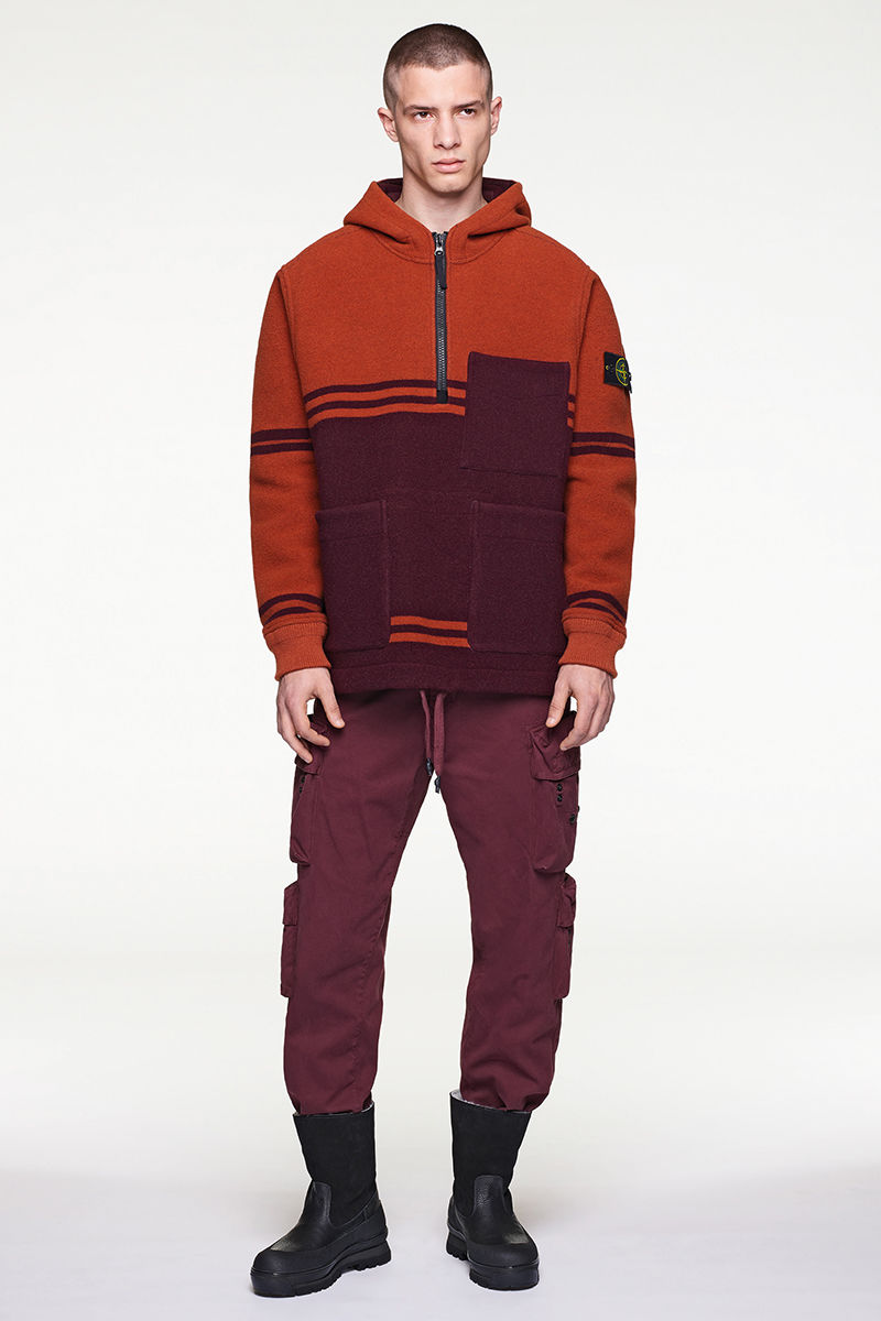 Model wearing red and burgundy hooded sweater, burgundy pants and black boots.