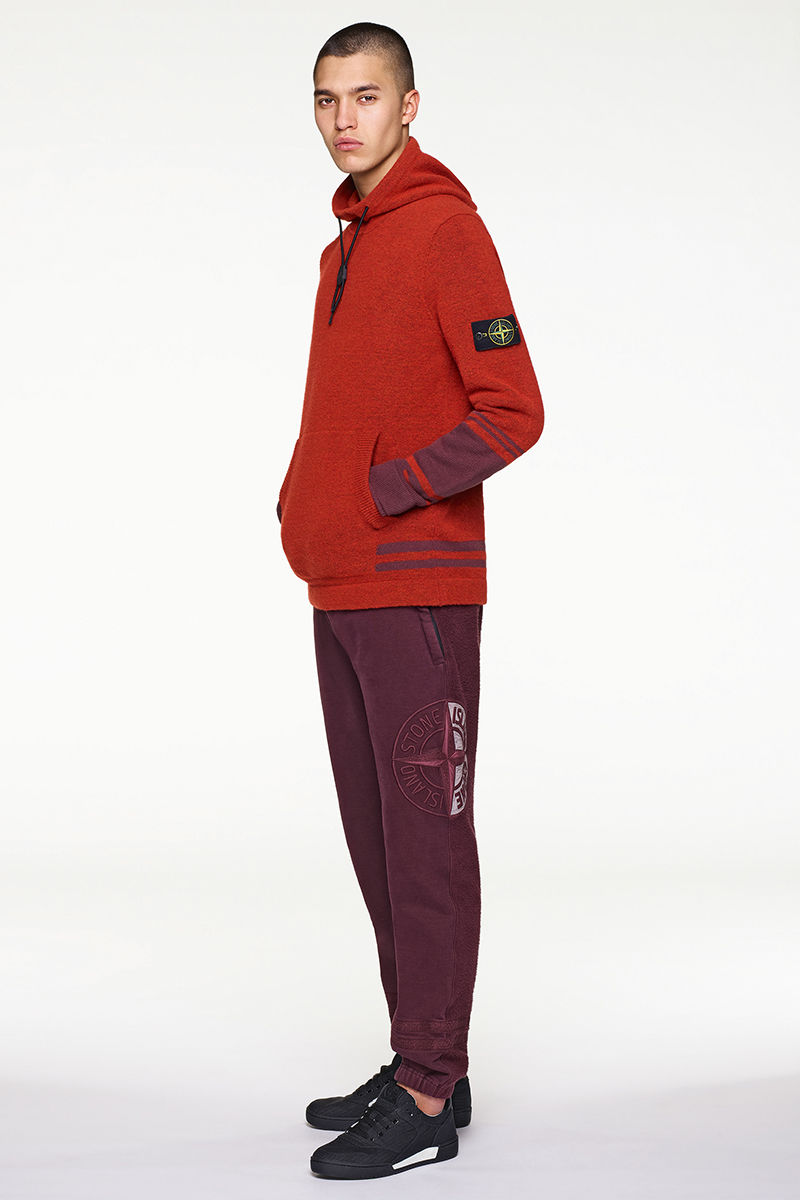 Model wearing red and burgundy hoodie with the Stone Island badge on left arm, burgundy pants and black sneakers.