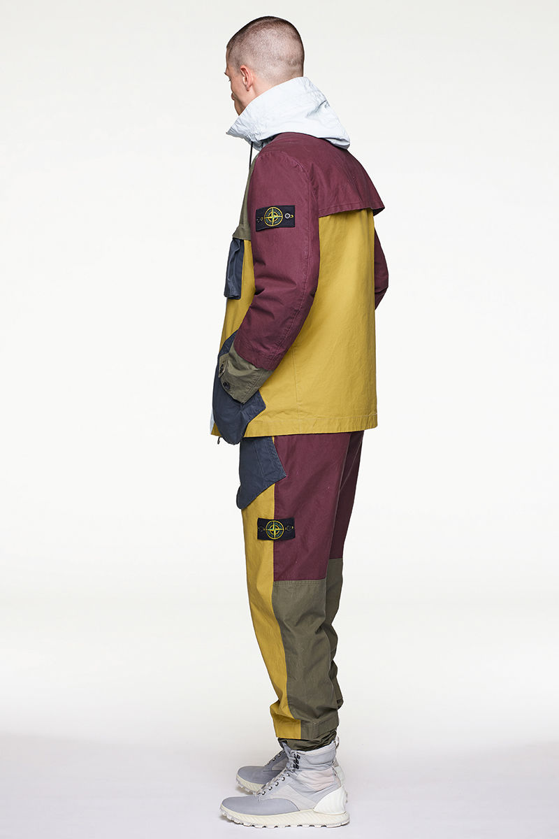 Side view of model wearing multi colored parka with white hood, matching pants and high top sneakers.
