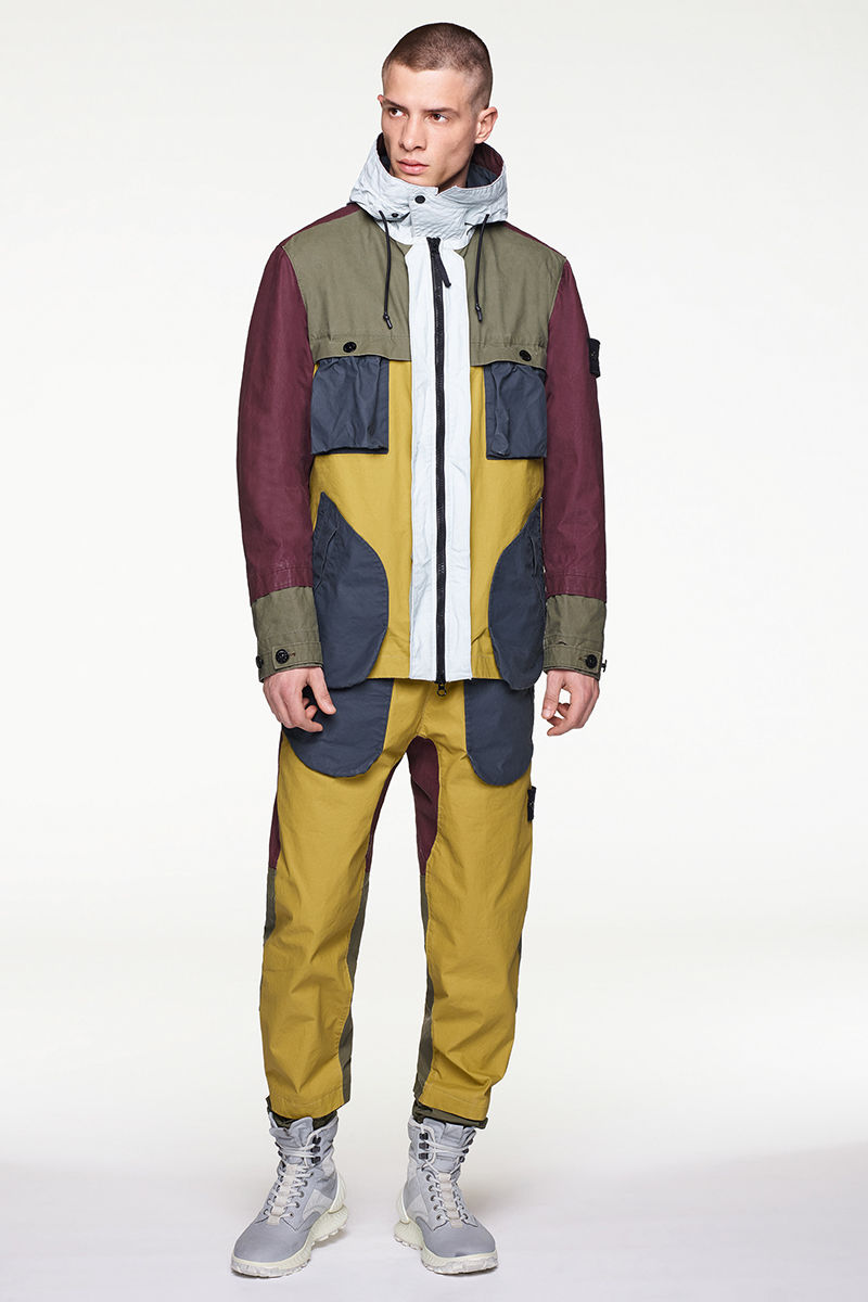 Front view of model wearing multi colored parka with white hood, matching pants and high top sneakers.