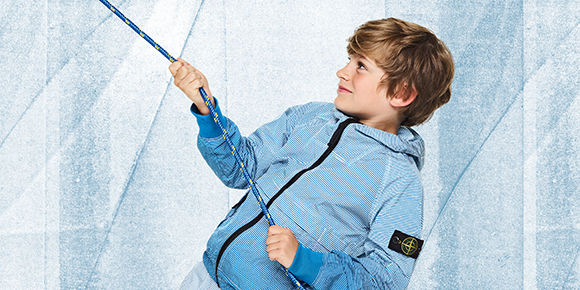 Junior model wearing light blue bomber jacket with hood, black zipper closure and detachable Stone Island badge on left sleeve.