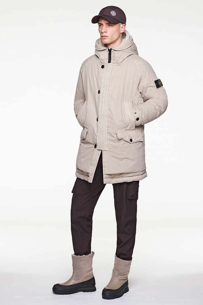 Model wearing sand colored quilted jacket, black pants, black cap and black and sand colored boots.