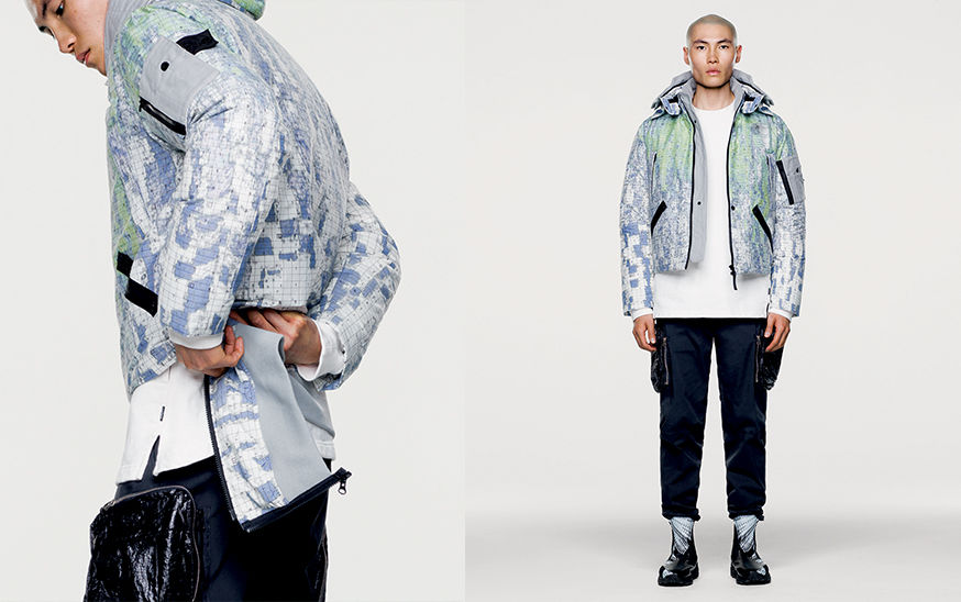 Side and front views of model wearing hooded, bomber jacket with graphic design and number print.