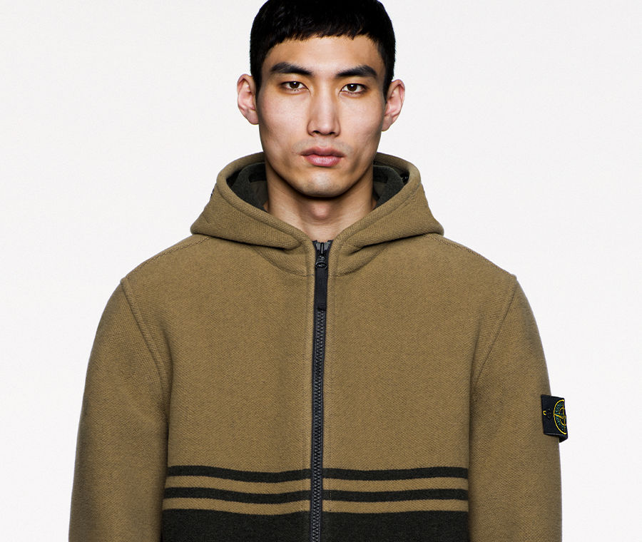 Model wearing green and dark green striped, hooded jacket with black zipper fastening with Stone Island badge on left arm.