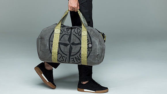 Model holding a gray duffle bag in Man Made Suede TC with green, nylon handles.