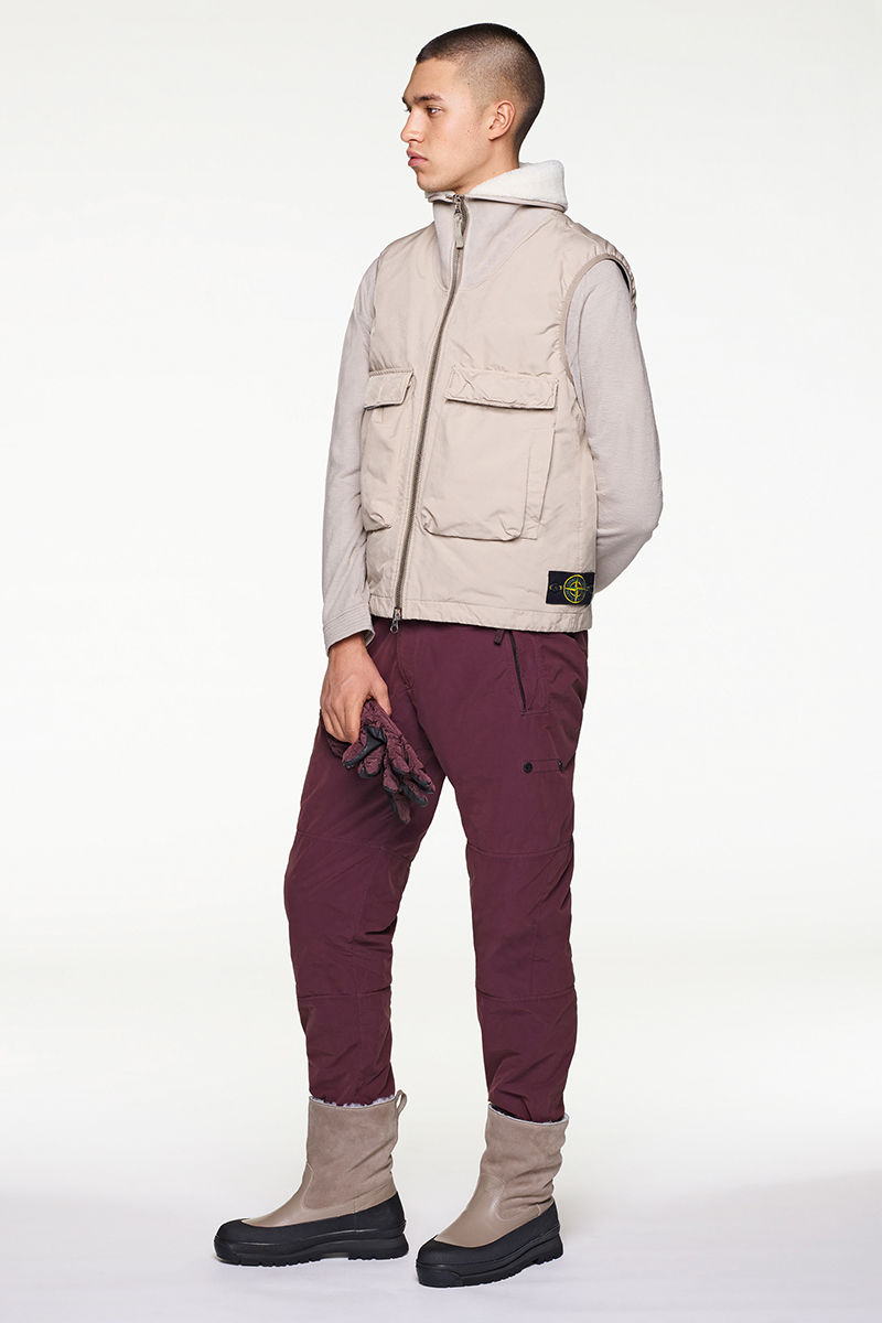Model wearing sand colored, quilted vest, dark burgundy pants and black and sand colored boots.