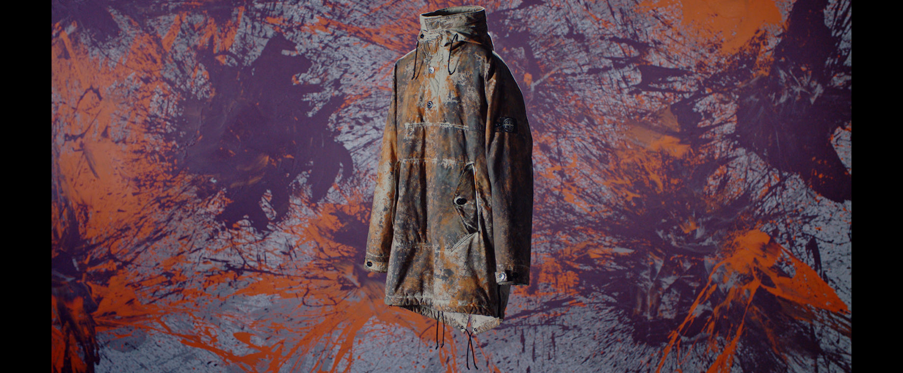 Camouflage print technical jacket with drawstring ties and a high collar, shown against abstract purple, grey, and red paint splatter background