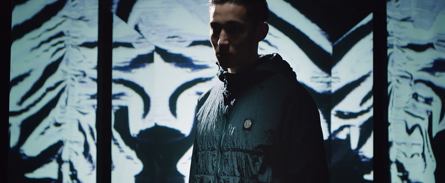 Model with face obscured by shadows wearing a dark toned technical jacket with Stone Island patch on the left side of the chest.