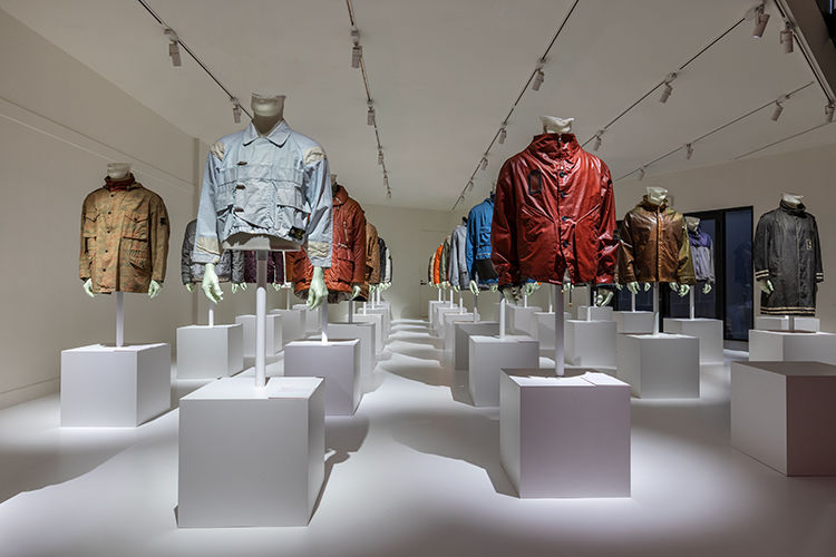 Artistic installation of several mannequins wearing Stone Island jackets from the Archive in different styles and colors, in a minimalist white room.