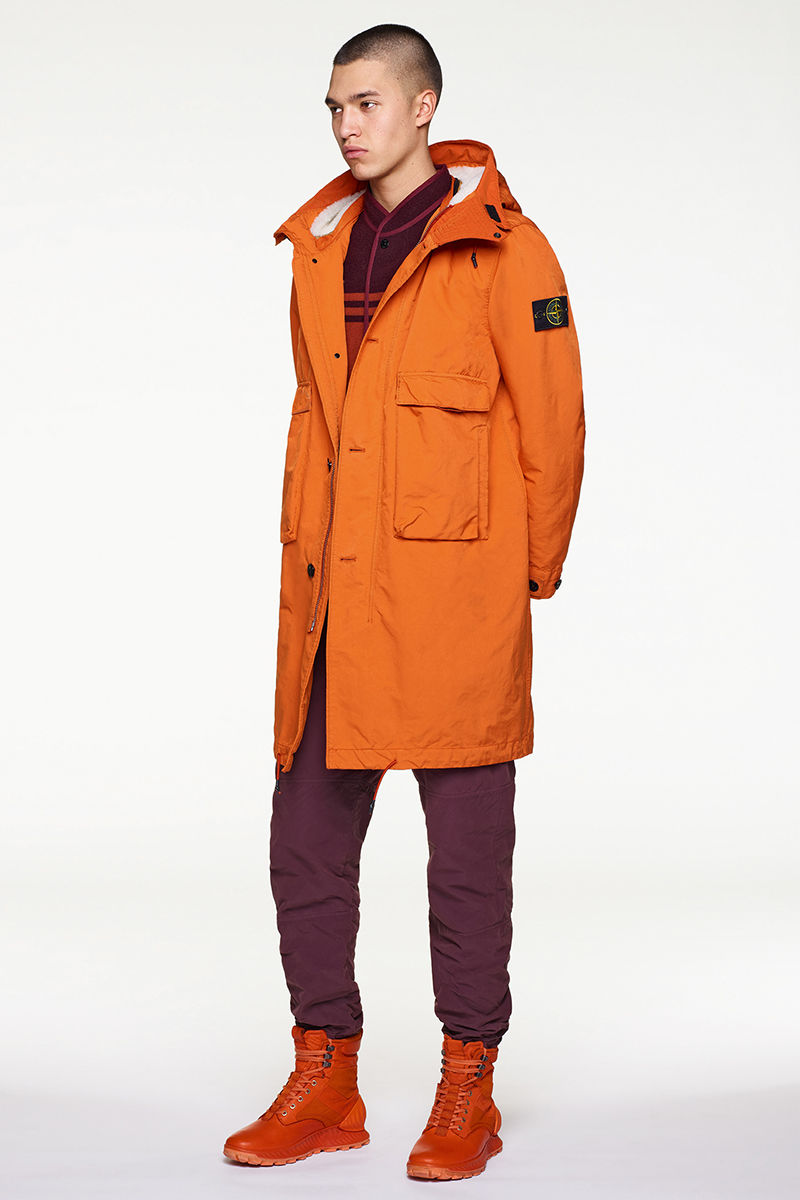 Model wearing orange parka over dark burgundy sweater and pants and orange high top sneakers.