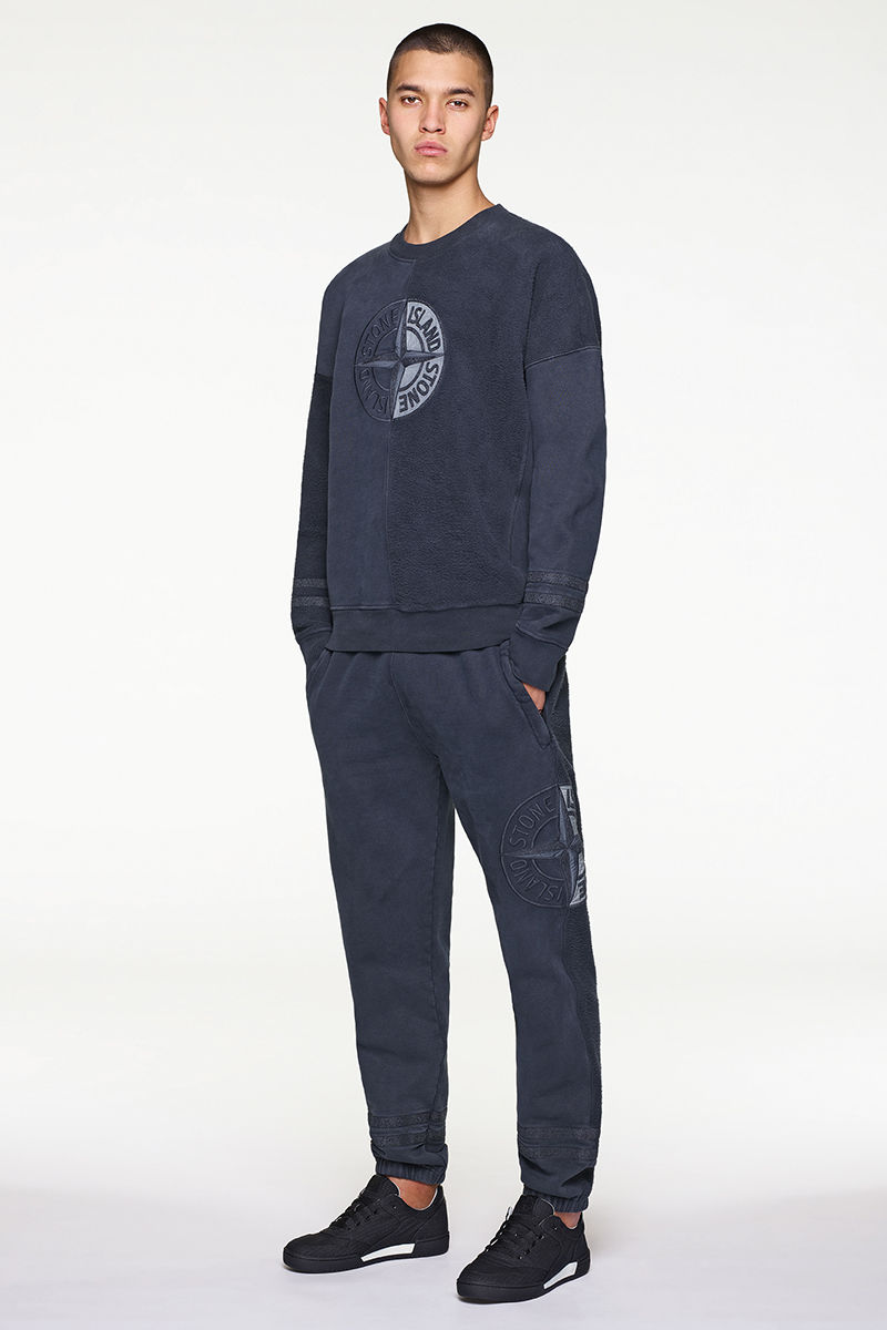 Model wearing dark blue sweater with the Stone Island compass rose at center chest, matching pants and black and white sneakers.