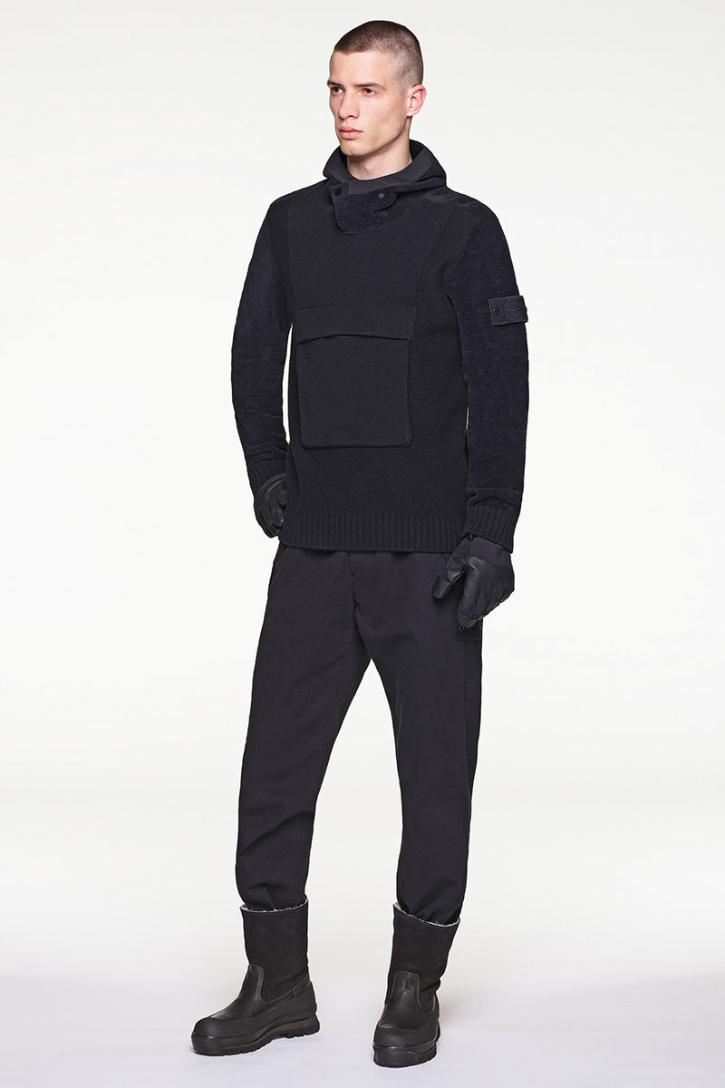 Model wearing black hoodie with central pouch pocket, black pants and black boots.