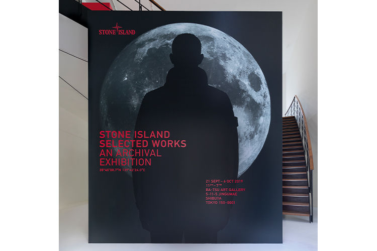 Stone Island archival exhibition board with model wearing a jacket, standing fully silhouetted against the moon.
