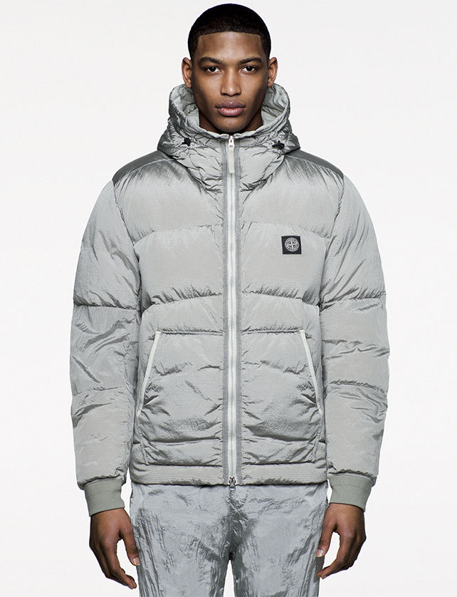 Model wearing silver puffer jacket with high collar and hood, diagonal welt pockets, and Stone Island patch on the left side of the chest.