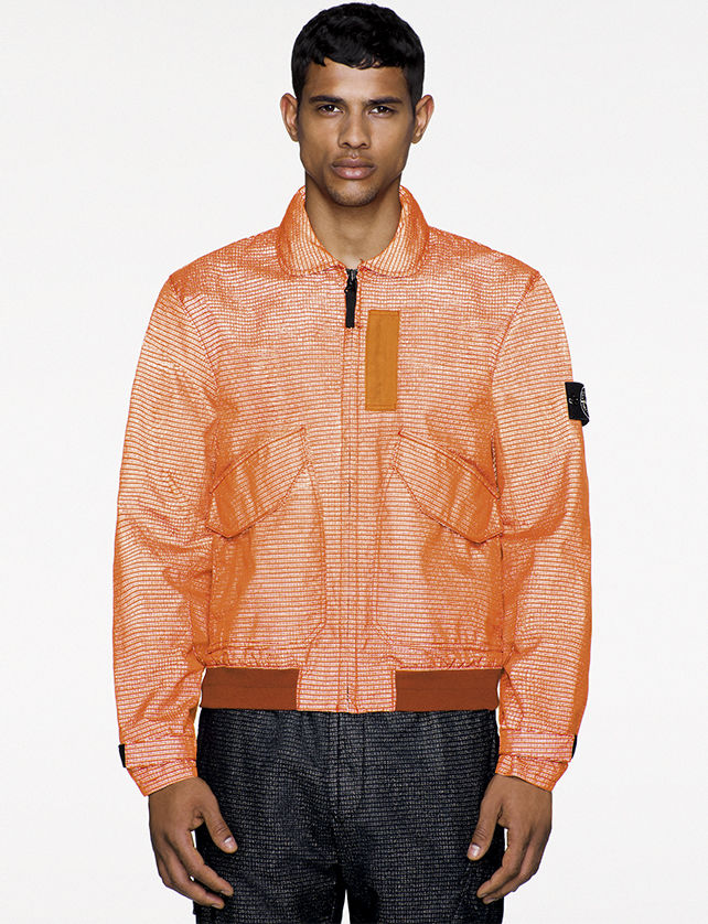 Model wearing orange reflective jacket with rounded collar, front zipper closure, two slanted patch pockets, and Stone Island badge on the upper left arm.