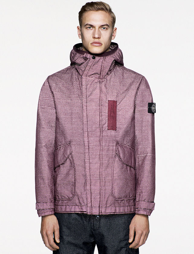 Model wearing maroon reflective hooded jacket with front zipper closure, two slanted patch pockets, and Stone Island badge on the upper left arm.