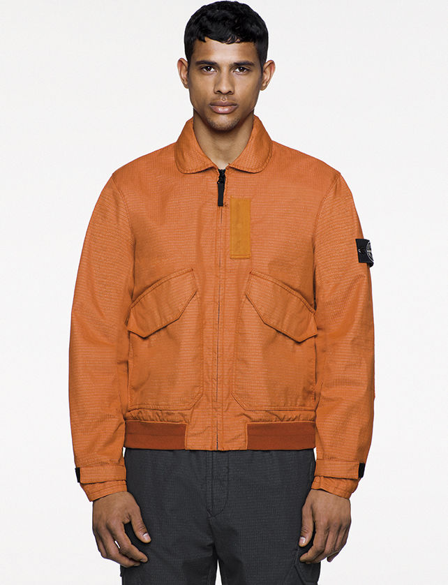 Model wearing orange jacket with rounded collar, black front zipper closure, two slanted patch pockets, and Stone Island badge on the upper left arm.