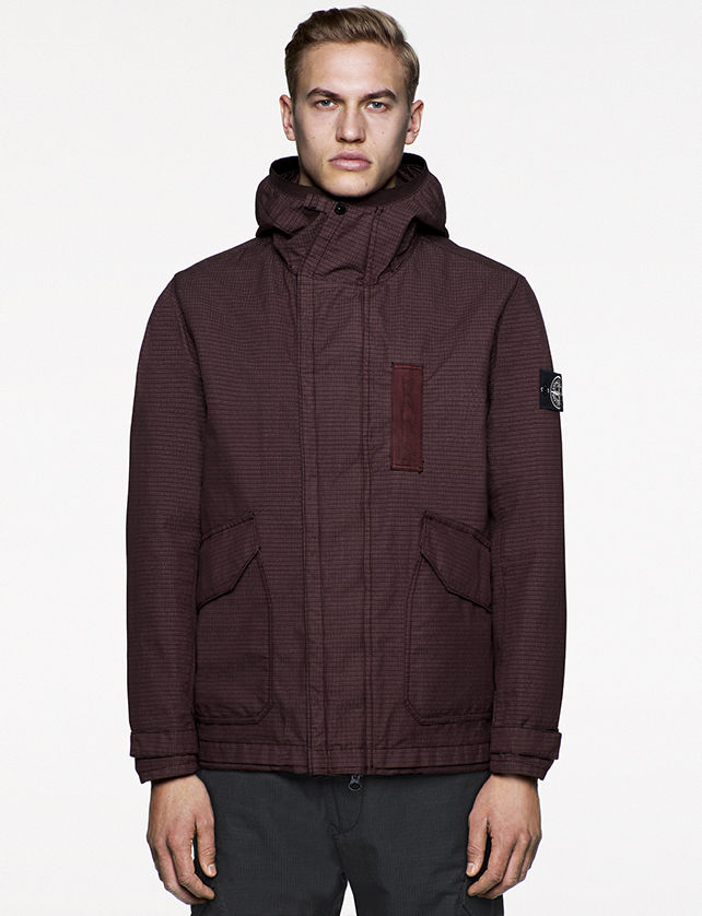 Model wearing dark maroon hooded jacket with front zipper closure, two slanted patch pockets, and Stone Island badge on the upper left arm.