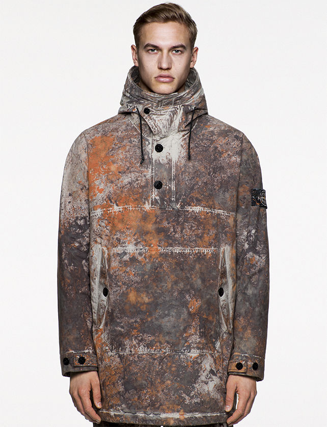 Model wearing hooded parka with multicolored camouflage spatters in earth tones, black buttons at the collar, kangaroo pocket and sleeve cuffs.