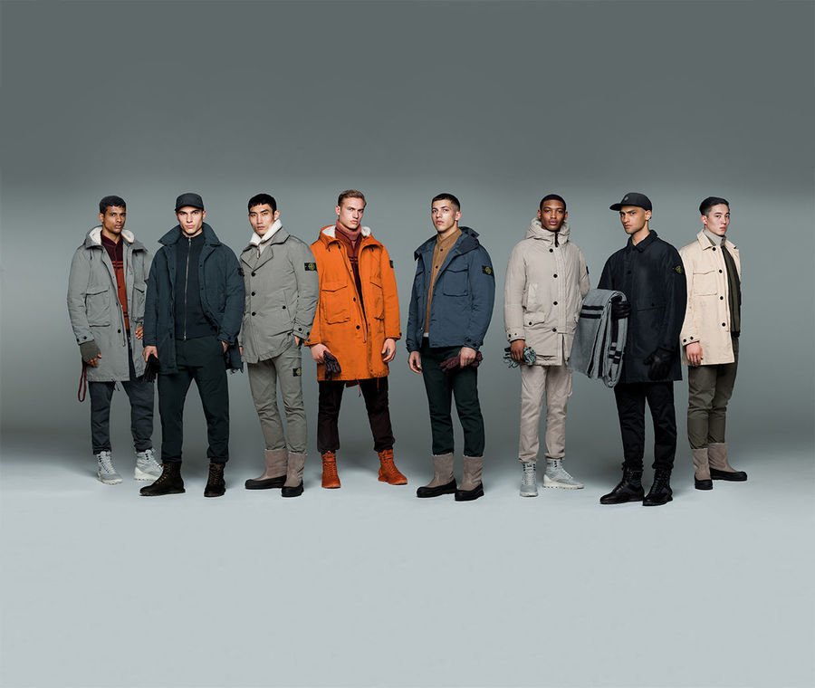 Eight models wearing Stone Island jackets, pants and caps in different styles and colors.