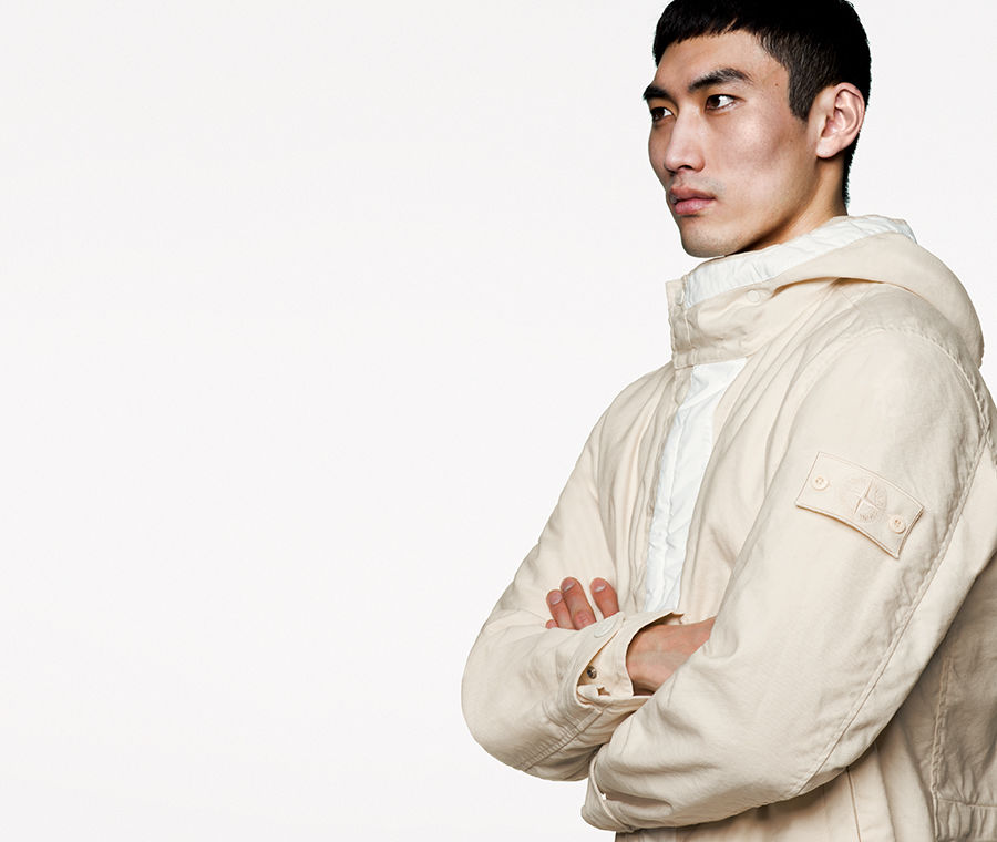Model wearing white hooded jacket with white ghost badge on left arm.