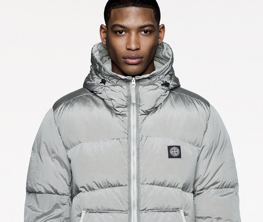 Model with arms folded wearing a silver puffer jacket with high collar and hood and Stone Island patch on the left side of the chest.