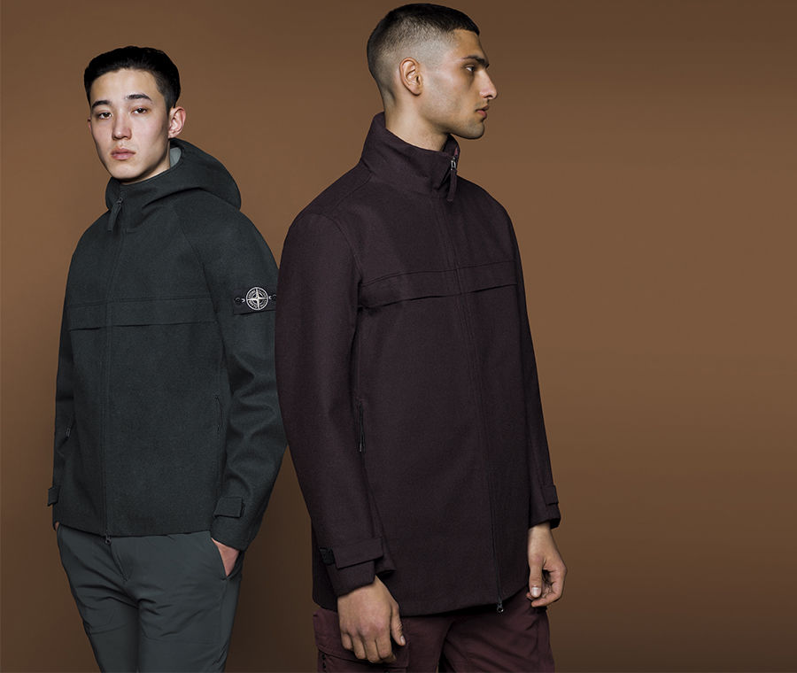 Two models wearing different styles of jackets in dark colors, one with hood and the Stone Island badge on upper left arm and the other with high collar.