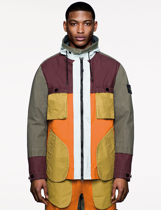 Model wearing multi colored jacket with large diagonal bellows pockets and matching pants.