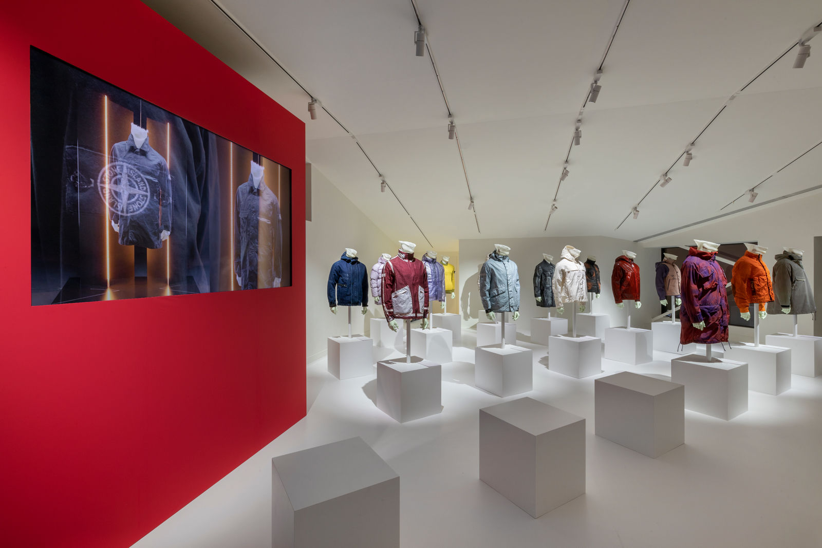 Exhibition space with mannequins wearing Stone Island jackets in different styles and colors on the right and a red panel with a large screen showing images of other mannequins on the left.