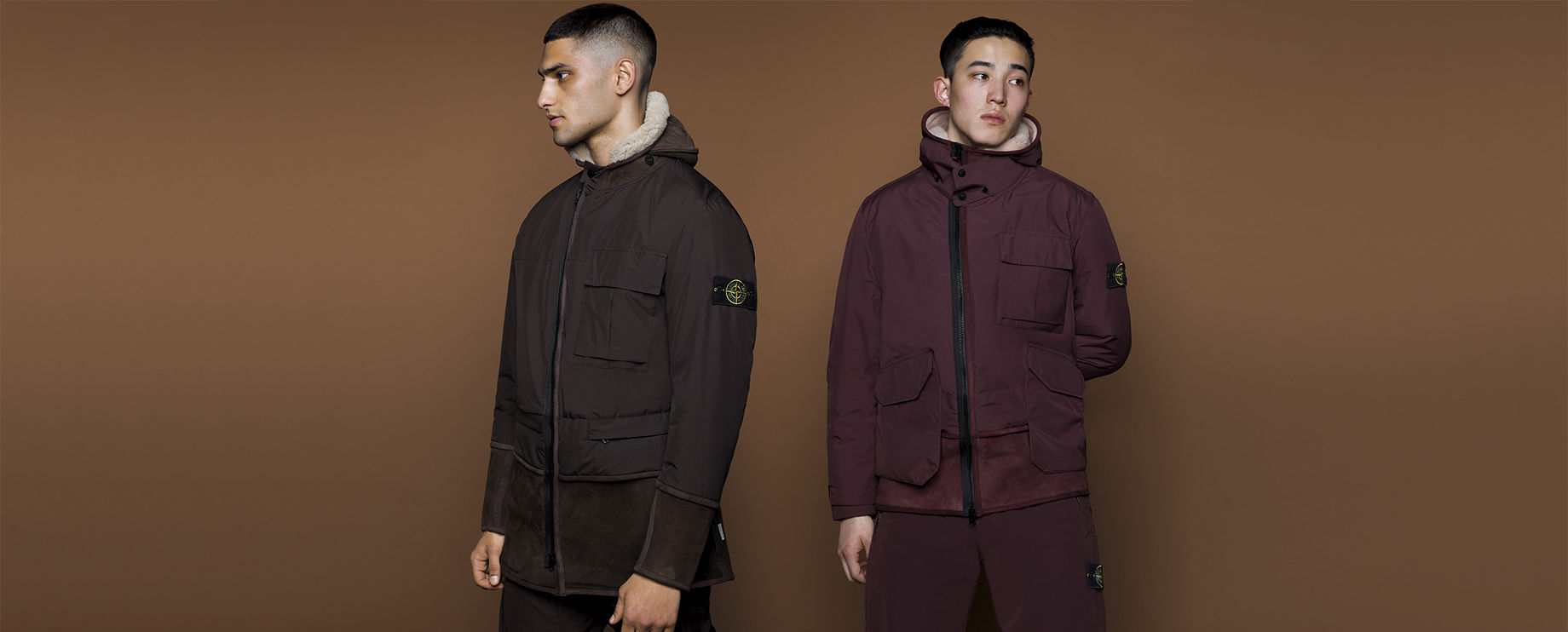 Model seen from the front, side and back, wearing black ankle boots, dark green hooded parka and matching pants, with Stone Island badge on left arm and thigh