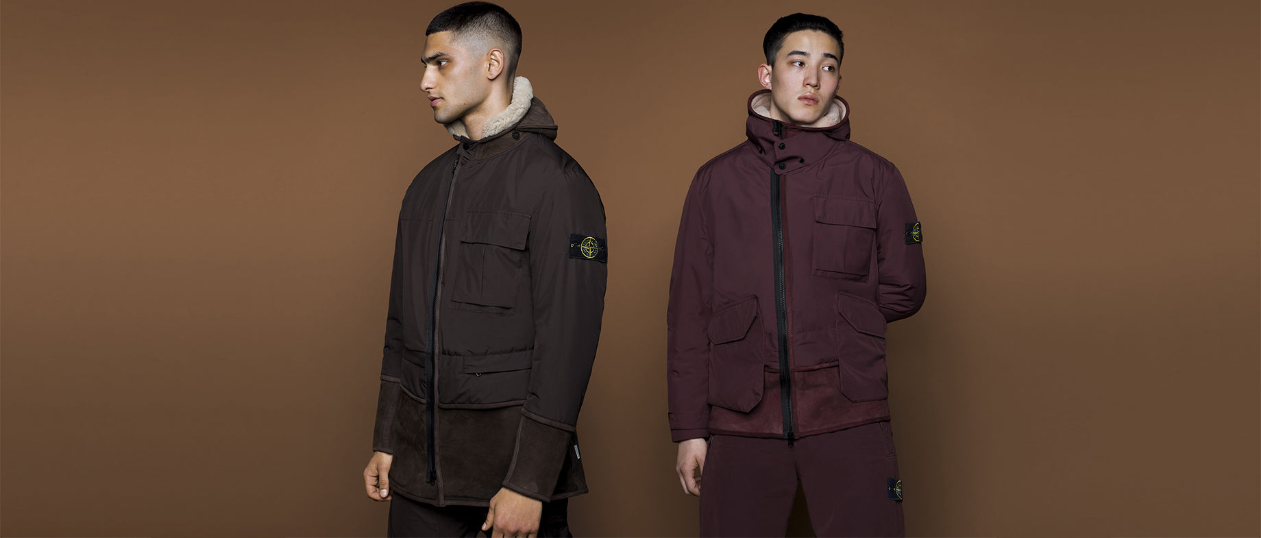 Two models wearing hooded parkas with patch pockets and black zippers, one in dark brown and one in burgundy