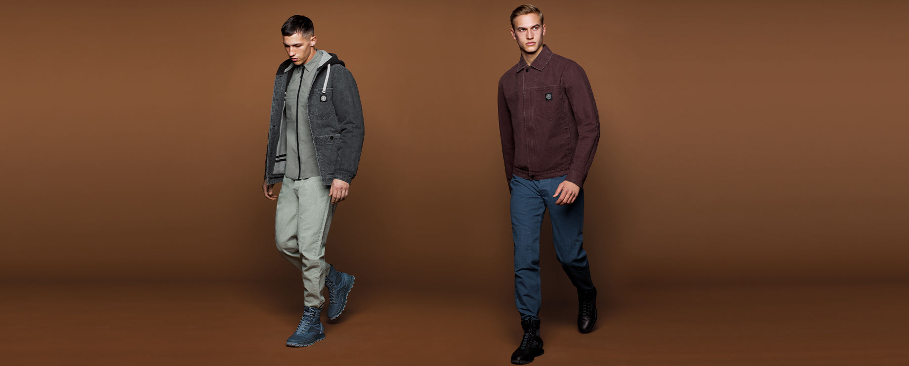Two models, one wearing a dark grey hooded parka and ankle boots, grey shirt and pants, the other wearing a burgundy collared jacket, blue pants, and black ankle boots