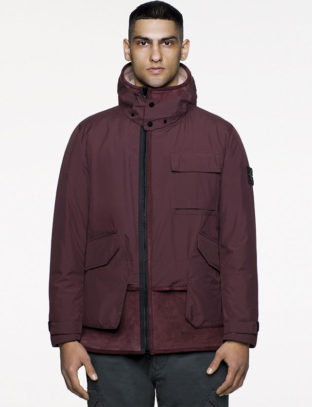 Model wearing hooded burgundy parka with black zipper, patch pockets, and Stone Island badge on the upper left arm