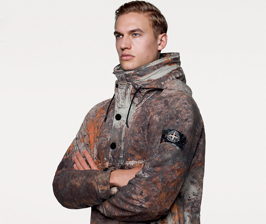 Portrait shot of model wearing hooded technical jacket with multicolored camouflage spatters in earth tones, black buttons on the front and the Stone Island badge on upper left sleeve.