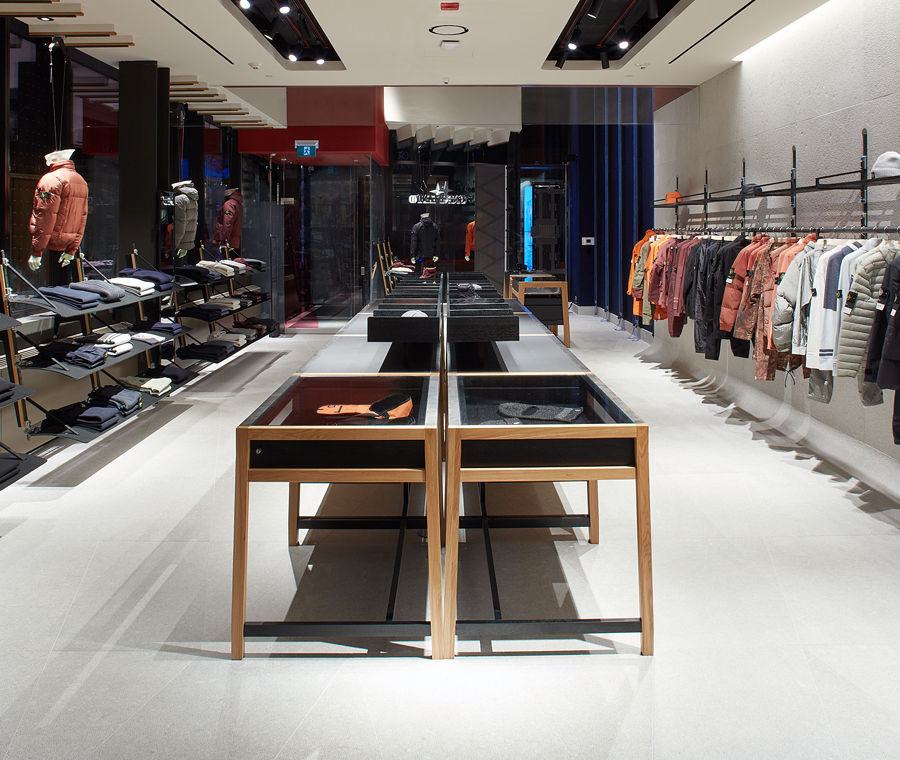 Interior view of the store facing the front entrance with jackets arranged by color hanging on a rack on the right, a display table in the center, folded clothes and mannequins facing windows on the left