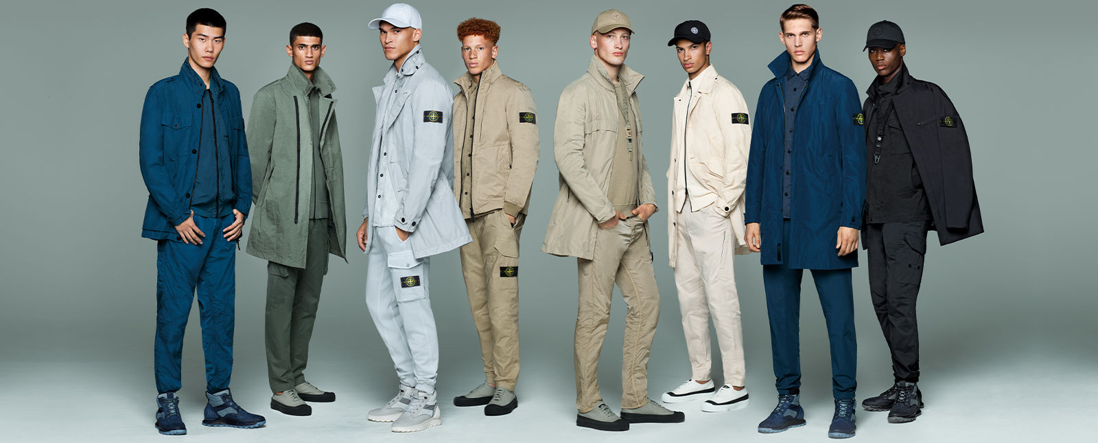 Eight models wearing monochrome outfits in dark blue, green, gray, tan, cream and black, composed of different styles of jackets, pants, shoes and caps.