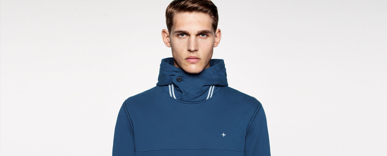 Portrait shot of a model wearing a blue jacket with white stripe details on the buttoned stand collar, with the Stone Island stella on the chest.